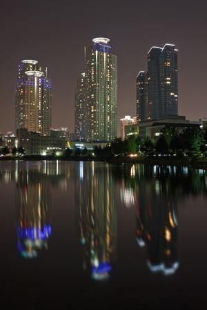 Illuminated apartments reflecting in a pond in night photo