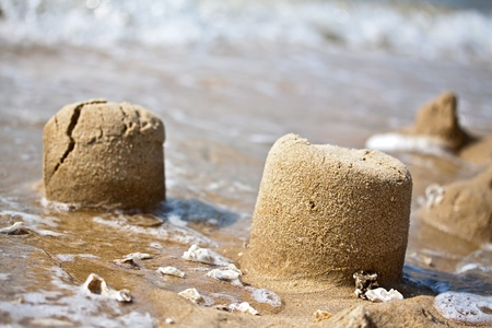 destroying: Sand pies at a sea coast dissolving by surf