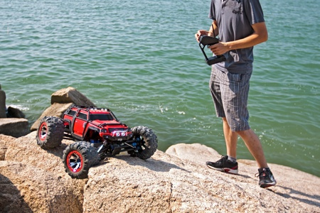 RC toy car on a rugged rock terrain with sea at background photo