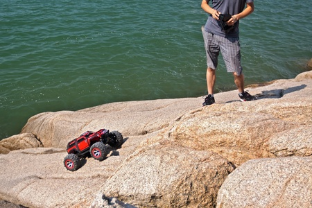 RC toy car on a stone terrain on sea background photo