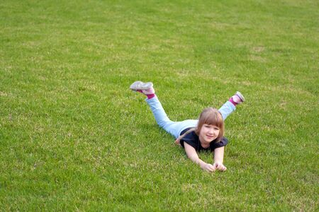 Smiling little girl lying on a lawn photo