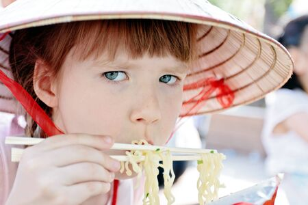 Young girl eating quick-cooking spaghetti in korean restaurant photo