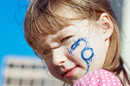 Close-up portrait of a little girl with blue dragon on her face photo