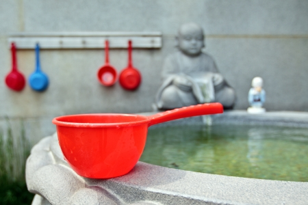 bailer: Red bucket for water in buddhist temple Stock Photo