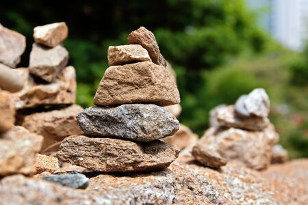 solidity: Small stone cairns in buddhist temples park Stock Photo