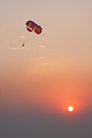 parasailing: Flight of parachute over sea on sunset