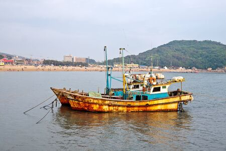 Anchored rusty fishing ships near Incheon (South Korea) photo