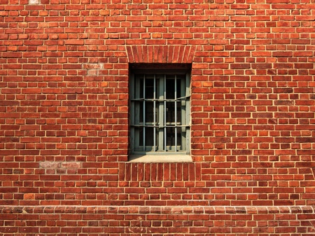penitentiary: Small window with lattice in a the red brick prison wall Stock Photo