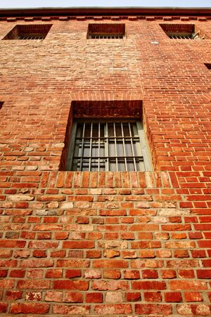 Windows on the red brick prison wall Stock Photo - 14173356