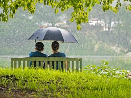 lluvia paraguas: Una pareja en un banco bajo el paraguas Foto de archivo