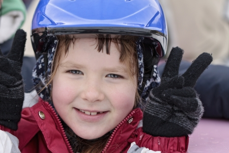 babys: Happy smiling girl 8 years old in blue helmet on a skating-rink Stock Photo