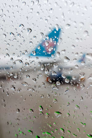 viewport: Water drops on an aircraft window with airplanes on a background