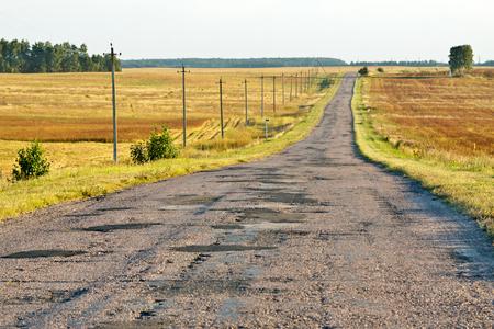 empedrado: Una vista persective carretera asfaltada en bruto en una campo en una tarde soleada