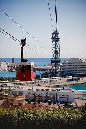 Red cabin on cable railways over Barcelona port Stock Photo