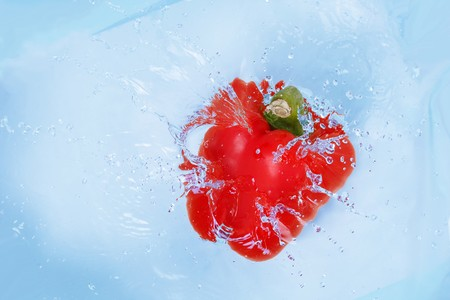 Red pepper falling into blue water Stock Photo