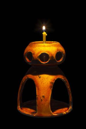 candlelit: Ceramic lamp with burning candle on black background