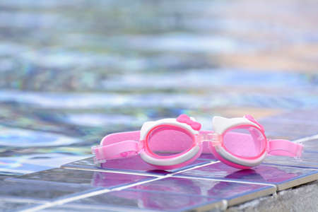 placed: The swimming glasses are placed beside pool.