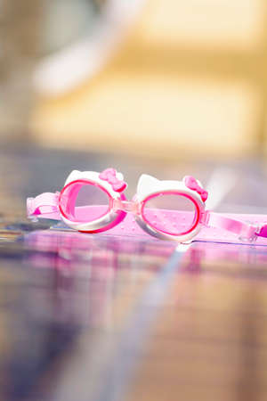 beside: The swimming glasses are placed beside pool.