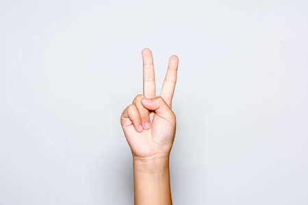 peace symbols: Boy raising two fingers up on hand it is shows peace strength fight or victory symbol and letter V in sign language on white background. Stock Photo