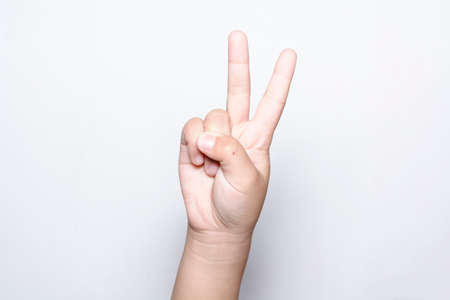 Girl raising two fingers up on hand it is shows peace strength fight or victory symbol and letter V in sign language on white background.