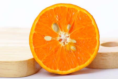 Orange shogun cut in half and cutting boards on a white background.