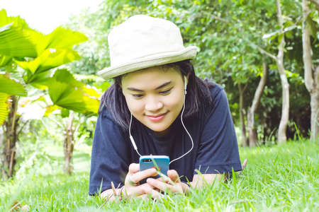 Young woman listening to music from your smart phone on the grass in the park.