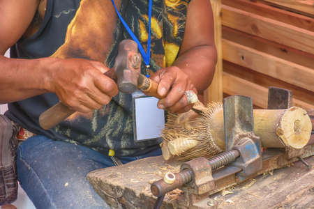The man is working wood. It is a craft.