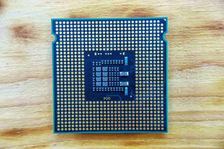 Old CPU socket 775 on a wooden background.