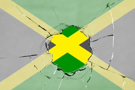 Flag of Jamaica on a on glass breakage. 版權商用圖片