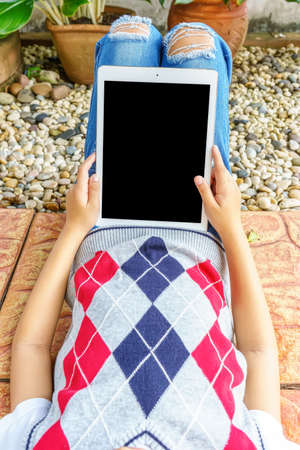 The girl slide on in mini garden with playing tablet pc.