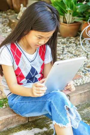 The girl sitting in mini garden with playing tablet pc.
