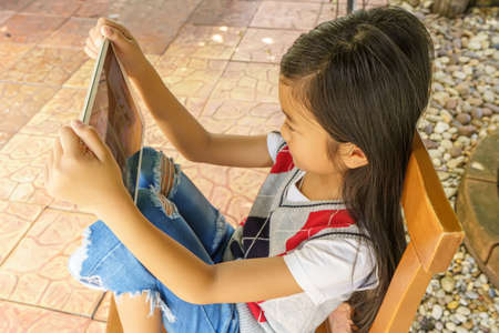 The girl sitting on wooden chair with playing tablet pc. 版權商用圖片