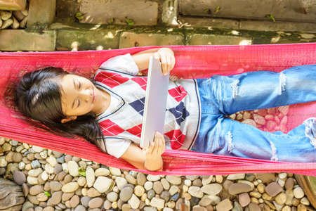 The girl lying in hammock with playing tablet pc.