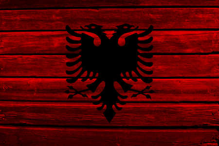 3D Flag of Albania on a old wood wall background.