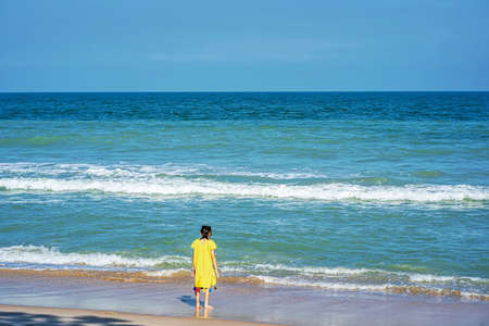 A girl standing on the beach in the morning on a fine day.
