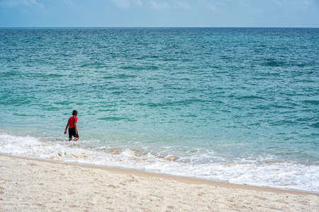 A boy playing in the sea in the morning on a fine day. Banco de Imagens