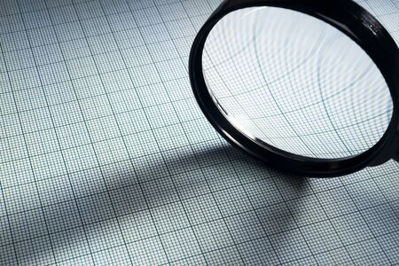 plotting: graph paper and magnifying glass, selective focus