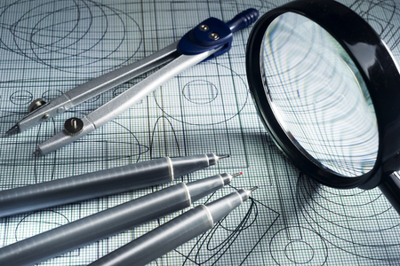 plotting: drawing,  magnifying glass, compasses and technical pen, selective focus Stock Photo