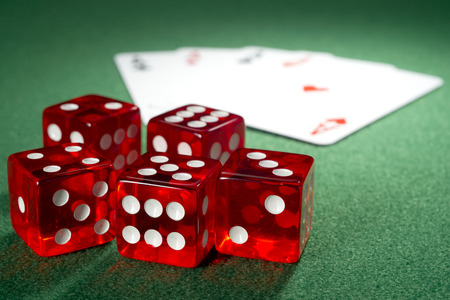 Red dice, four aces  on a green felt photo
