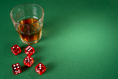 red dice: Red dice and glass of whiskey on a green felt