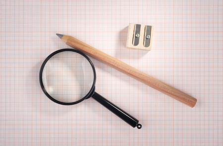 plotting: magnifying glass, pencil and sharpener over graph paper, selective focus