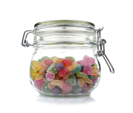 Candies in glass jar , isolated on white photo