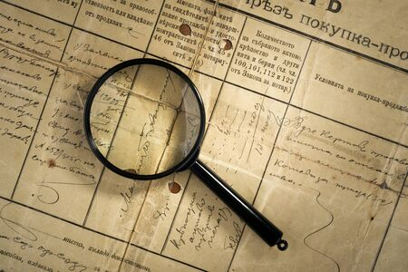 old deed property and magnifying glass photo