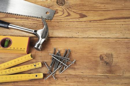 herramientas de trabajo: Serrucho, martillo, nivel, u�as y plegable regla sobre fondo de madera