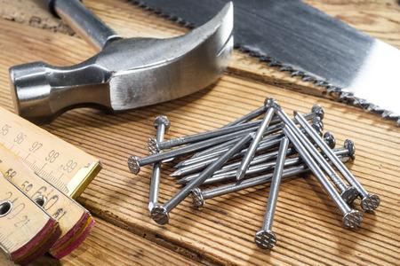 serrucho: Serrucho, martillo, clavos y plegable regla sobre fondo de madera