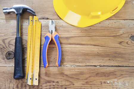 nippers: hammer, folding ruler, nippers and yellow helmet  on wooden background Stock Photo