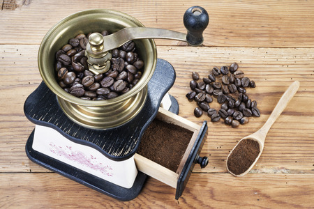 manual coffee grinder with coffee beans on wooden table