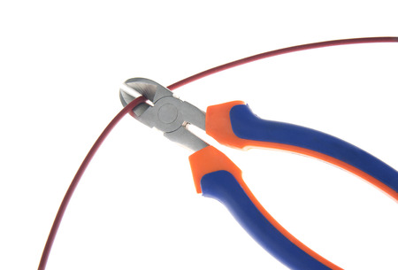 disconnecting: Metal nippers is cutting red cable on white background Stock Photo