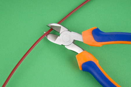 disarm: Metal nippers is cutting red cable on green  background Stock Photo