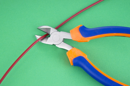 disconnecting: Metal nippers is cutting red cable on green  background Stock Photo
